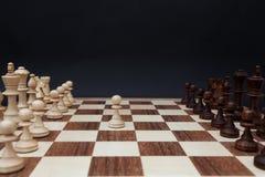 Erste Bewegung durch weißes Pfand auf der Mitte des Brettes Schachbrett auf einem schwarzen Hintergrund Stockfotografie