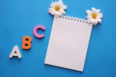 Erste Buchstaben ABCs-d des englischen Alphabetes auf einem blauen Hintergrund Notizbuch und weiße Chrysantheme Leerer Platz f?r  lizenzfreie stockfotografie