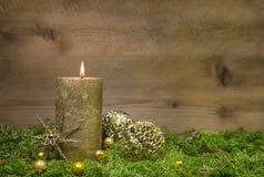 Erste Einführung: goldene Kerze, die vor hölzernem Hintergrund brennt Stockbilder
