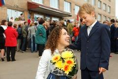 Erste Klasse, Junge und seine Mutter mit Blumenstrauß Stockfotos