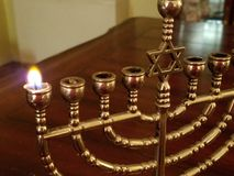Erste Nacht der Hanukka, die erste Kerze des menorah lizenzfreie stockfotografie