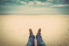 Erste Personenperspektive von Mannbeinen in den Jeans auf dem Herbststrand Stockfotografie