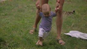 Erste Schritte des Babys auf Gras stock footage