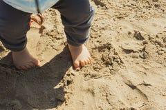 Erste Schritte des Babys im Sand des Strandes Stockfotografie