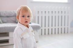Erste Schritte des Babys lernend, in weißes sonniges Schlafzimmer zu gehen Lizenzfreies Stockfoto