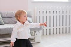 Erste Schritte des Babys lernend, in weißes sonniges Schlafzimmer zu gehen Stockbild