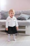 Erste Schritte des Babys lernend, in weißes sonniges Schlafzimmer zu gehen Stockbilder