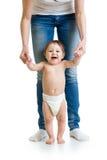 Erste Schritte des Babys mit Mutterhandunterstützung Stockbild