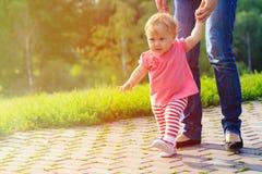 Erste Schritte des kleinen Mädchens mit Mutter draußen Stockfoto