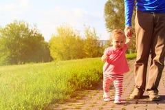 Erste Schritte des kleinen Mädchens mit Vati im Park Lizenzfreie Stockfotos