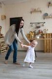 Erste Schritte des Mutter-und Baby-Kleinkindmädchens, wirklicher Innenraum des Lebensstils, Stockbilder