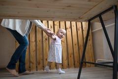 Erste Schritte des Mutter-und Baby-Kleinkindmädchens, wirklicher Innenraum des Lebensstils, Lizenzfreie Stockfotografie