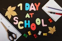 Erste Tagesin der schule Aufschrift gemacht von farbigen Buchstaben, von Schulbedarf und von Herbstlaub auf dem schwarzen Hinterg Lizenzfreie Stockfotografie