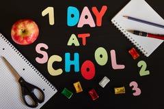 Erste Tagesin der schule Aufschrift gemacht von farbigen Buchstaben, vom Schulbedarf und vom reifen roten Apfel auf dem schwarzen Stockbilder