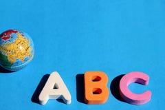 Erster Buchstabe ABCs des englischen Alphabetes und eine kleine Kugel auf einem blauen Hintergrund Leerer Platz f?r Text Lernen v lizenzfreie stockbilder