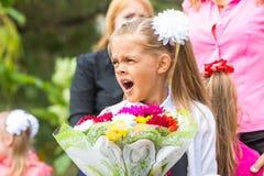 Erster Sortierer mit Blumenstrauß von Blumen gähnt in der Schule in einer Menge Lizenzfreie Stockfotografie