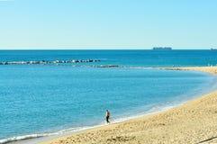 Erstes Bad in verlassenem blauem Strand Stockfoto