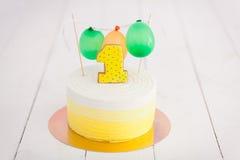 Erstes Geburtstagszertrümmern der Kuchen Der Kuchen mit Nummer Eins und wenig Ballons Drei Bandpartner singen und spielen Gitarre Stockbild
