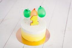 Erstes Geburtstagszertrümmern der Kuchen Der Kuchen mit Nummer Eins und wenig Ballons Drei Bandpartner singen und spielen Gitarre Lizenzfreies Stockfoto