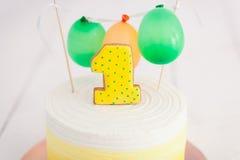 Erstes Geburtstagszertrümmern der Kuchen Der Kuchen mit Nummer Eins und wenig Ballons Drei Bandpartner singen und spielen Gitarre Stockfoto