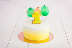 Erstes Geburtstagszertrümmern der Kuchen Der Kuchen mit Nummer Eins und wenig Ballons Drei Bandpartner singen und spielen Gitarre Lizenzfreie Stockfotografie