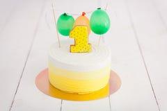 Erstes Geburtstagszertrümmern der Kuchen Der Kuchen mit Nummer Eins und wenig Ballons Drei Bandpartner singen und spielen Gitarre Stockfotos
