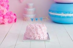 Erstes Geburtstagszertrümmern der Kuchen Ein rosa Kuchen steht auf einem weißen hölzernen Hintergrund Erster Geburtstag Stockbild