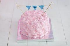 Erstes Geburtstagszertrümmern der Kuchen Ein rosa Kuchen steht auf einem weißen hölzernen Hintergrund Erster Geburtstag Stockfotos