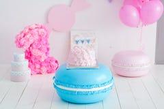 Erstes Geburtstagszertrümmern der Kuchen Ein rosa Kuchen steht auf einer großen blauen Makrone Erster Geburtstag Stockbild