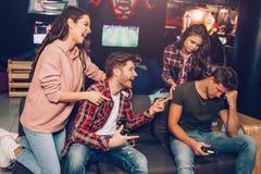 Erstes Paare laughingg auf zweitem Sie gewinnen Spiel Leute sitzen im Raum Kerle halten Steuerknüppel lizenzfreie stockbilder