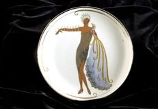Erte Diva 2. Erte artwork deco collectible plate on black velvet background the Diva II with a tiara and flowing gown in a symmetrical design stock image