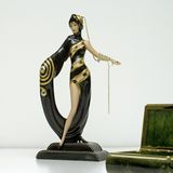 Erte figurine deco square. Close-up standing retro Erte geometric statue Pearls and Emeralds art deco female statue figurines with long pearls wrapped around arm royalty free stock image