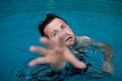 Ertrinken des kaukasischen Mannes im Swimmingpool bitten um Hilfe Er seine Hände in der Furcht ausdehnend lizenzfreie stockfotos