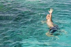 Ertrinken des Mannes im Meer bitten um Hilfe mit den angehobenen Armen Der Mann ertrinkt im Meer Vertikales Foto lizenzfreie stockfotos