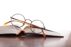 Erudite. Open book and glasses with circular rim on a white background Royalty Free Stock Image