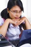 Erudito femminile che esamina il suo computer portatile Fotografia Stock