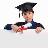 Erudito graduado que señala a la tarjeta blanca Fotografía de archivo libre de regalías