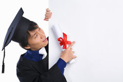 Erudito graduado que señala a la tarjeta blanca Imagenes de archivo