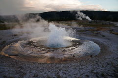 Erupción del géiser: las nubes reflejaron en una charca de la salida de las aguas termales rodeada por la corteza hidrotérmica bl