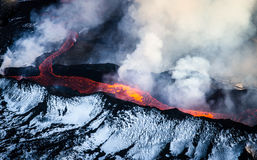 Erupting volcano in Iceland. Aerial photo of snow-covered Bardabunga volcano erupting in Iceland, hot lava melting ice, steam and sulphuric gases rising up Royalty Free Stock Images