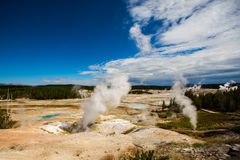Eruption of the geothermal in yellowstone park. Eruption of the geothermal under blue sky in yellowstone park royalty free stock image
