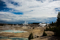 The geothermal in yellowstone park. Eruption of the geothermal under blue sky in yellowstone park stock photo