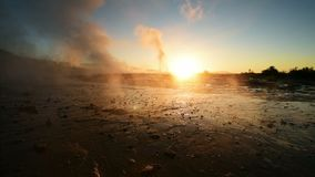 Eruption of geyser in Iceland. Winter cold colors, sun lighting through the steam stock video