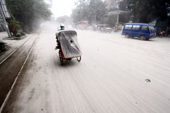 Eruption of Mount Kelud. A pedicab makes its way on a street covered with volcanic ash from an eruption of Mount Kelud, in Solo, Indonesia, Friday, Feb. 14, 2014 royalty free stock photo