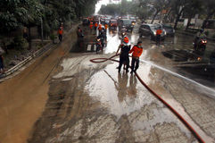 Eruption of Mount Kelud. Some volunteers cleaning road covered in ash volcanic from an eruption of Mount Kelud that closed the road Slamet Riyadi, Solo, Central royalty free stock photos