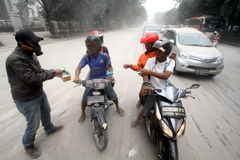 Eruption of Mount Kelud. Some volunteers handing out masks to road users in the event of rain ash volcanic from an eruption of Mount Kelud that closed the road royalty free stock image
