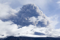 Eruzione del vulcano in cenere e cielo blu dell'Islanda Immagine Stock