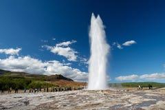 Eruzione di Strokkur con i turisti che aspettano intorno, cerchio dorato Immagine Stock