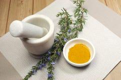 Erva de Rosemary e especiaria da cúrcuma com almofariz e pilão Foto de Stock