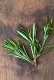 Erva dos alecrins limitada em um fundo de madeira com espaço da cópia Rosemary fresco Vista superior imagem de stock